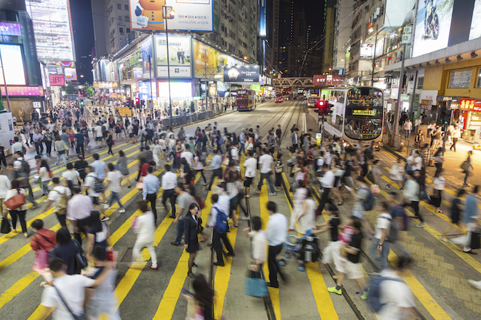 HONG KONG, HONG KONG - SEPTEMBER 23 2015: Pedestrians rush through a very busy intersection in the shopping district of Causeway Bay in Hong Kong island at night.